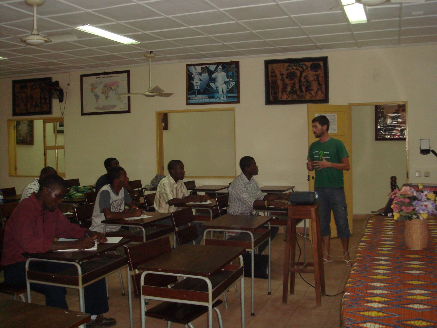 Portuguese guy holding is standing in a class room and gives a presentation in front of African school children.