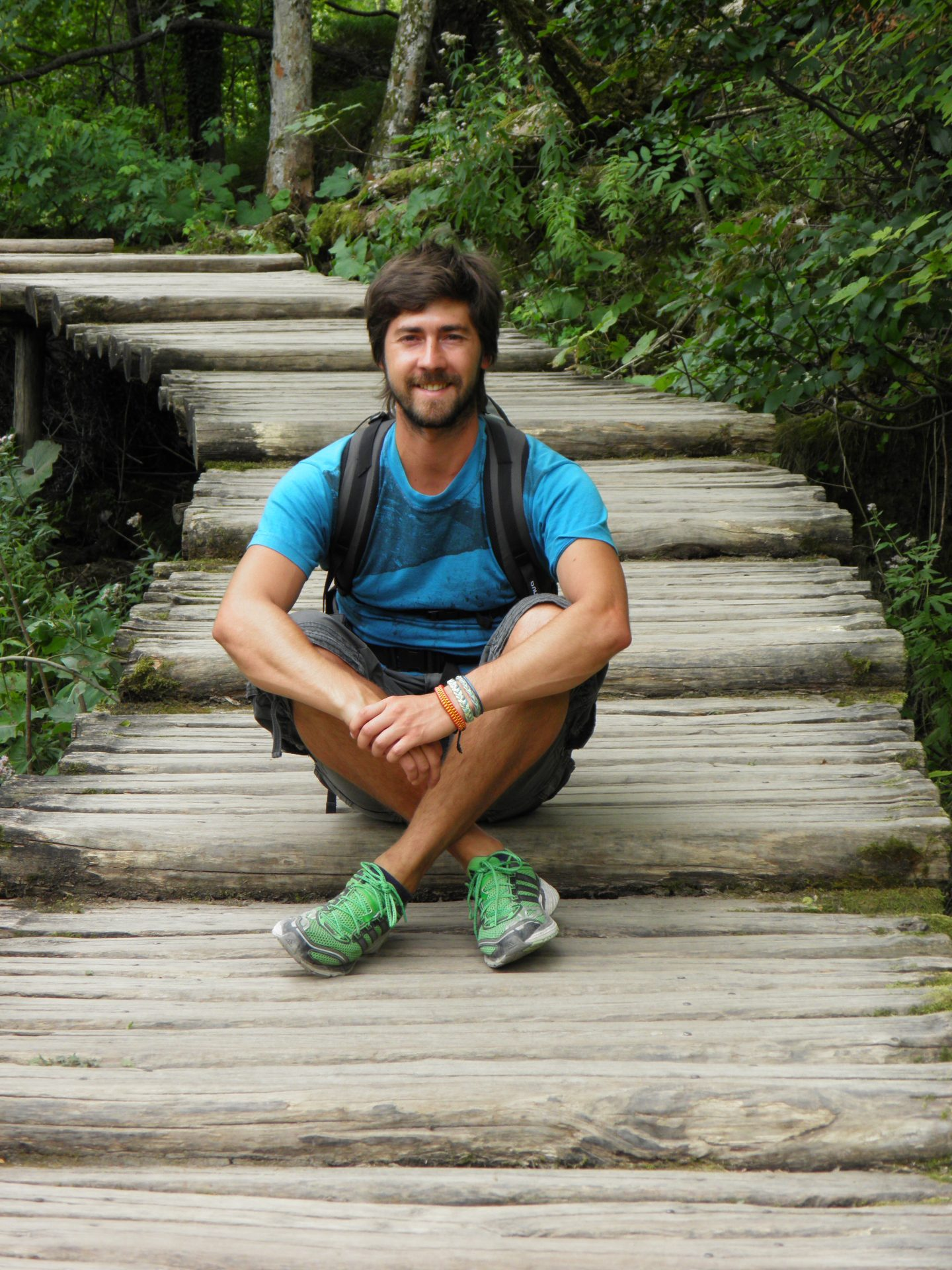 Guy sitting on the stairs smiling into the camera.