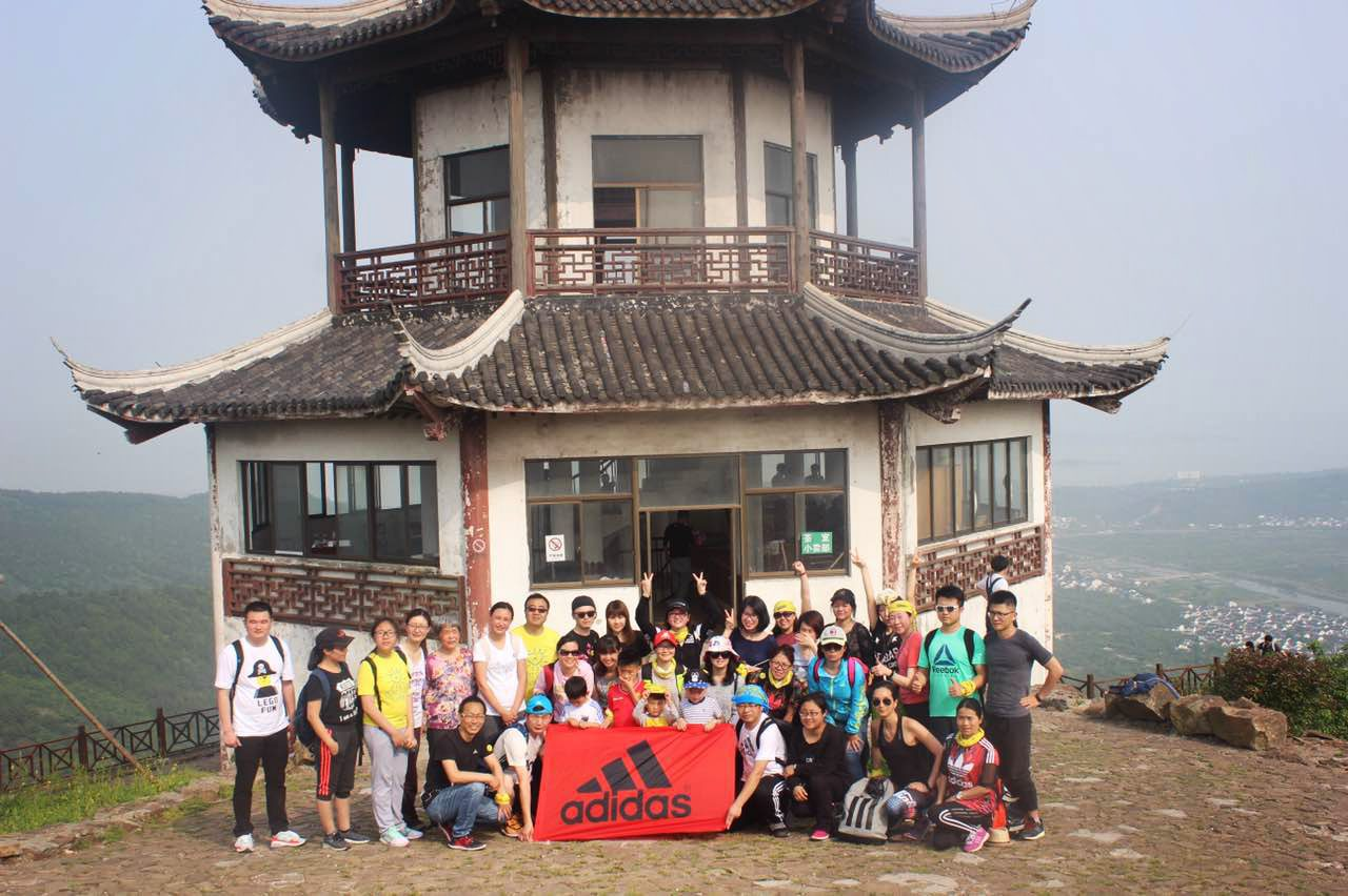 team posing on mountain with adidas flag trainee shanghai experience