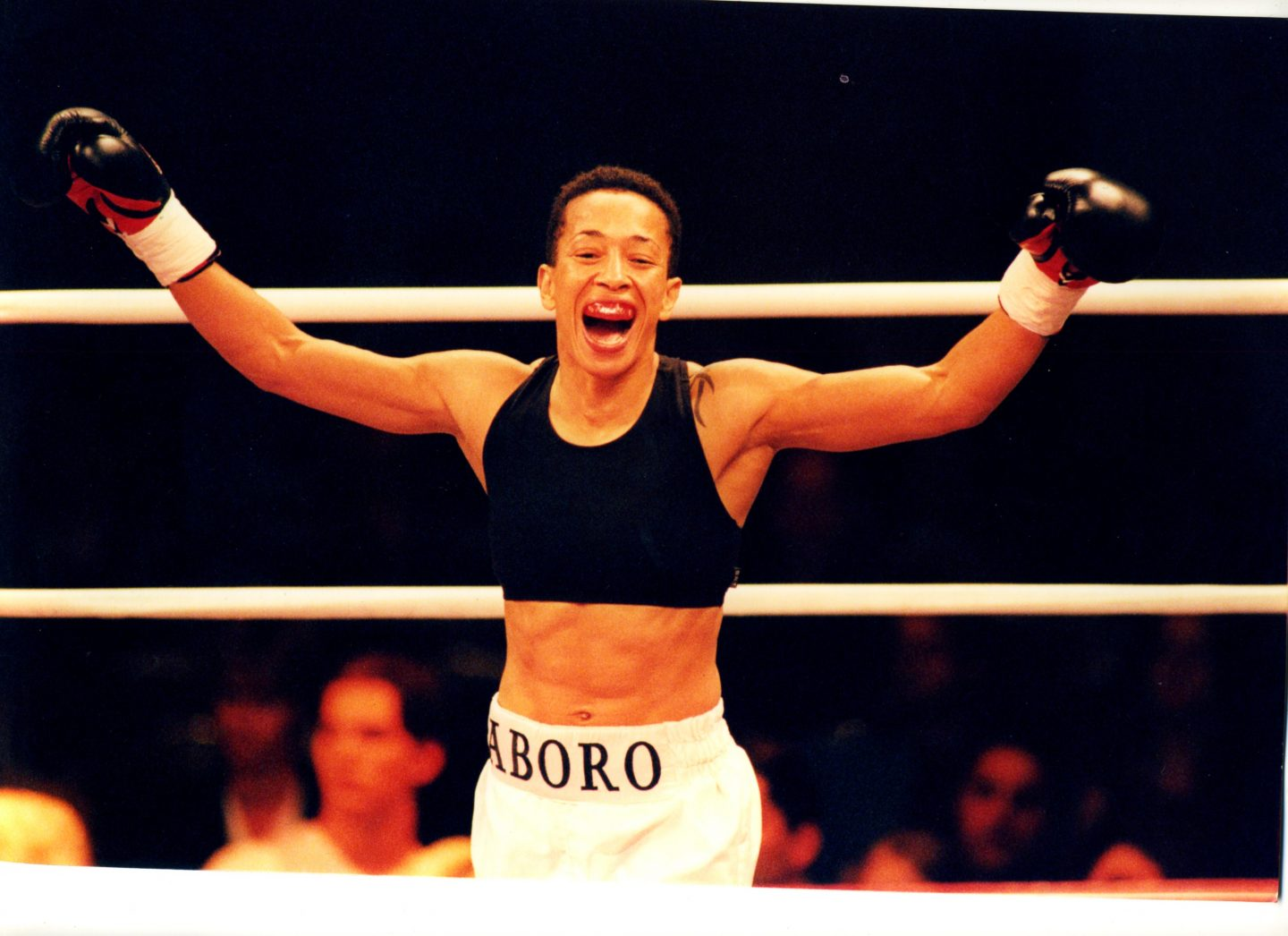 Michele-Aboro-boxing-winning-vicotry-pose-smiling-black-shirt-white-shorts