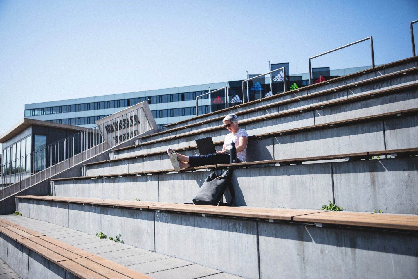 Girl working in the stadium stands with laptop, Work,Outside,Stadium, Stands, adidas, GamePlanA