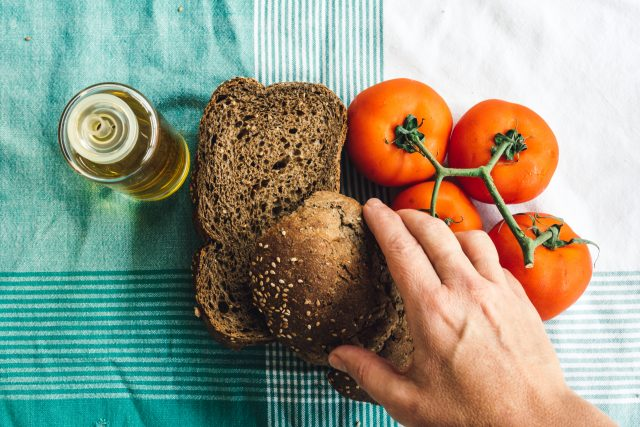 Hand over on Olive oil, tomato and slides of brown bread on tablecloth. Top view, nutrition, health, business, fitness, GamePlan A, adidas