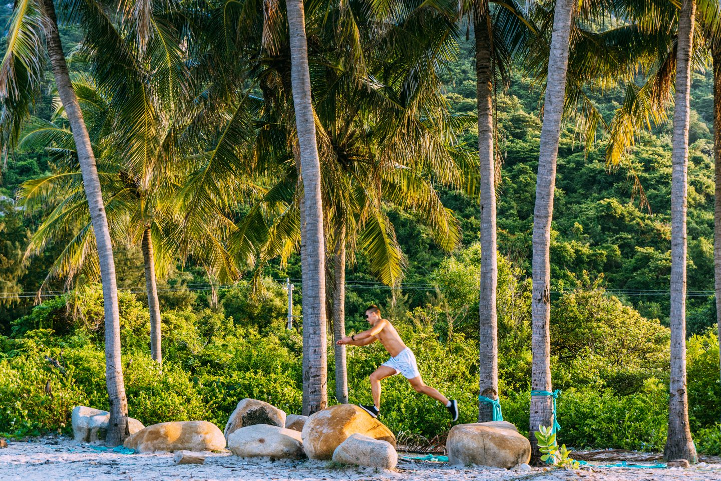 Man running and jumping from rock to rock at a beach. In the background one can see huge palm trees.