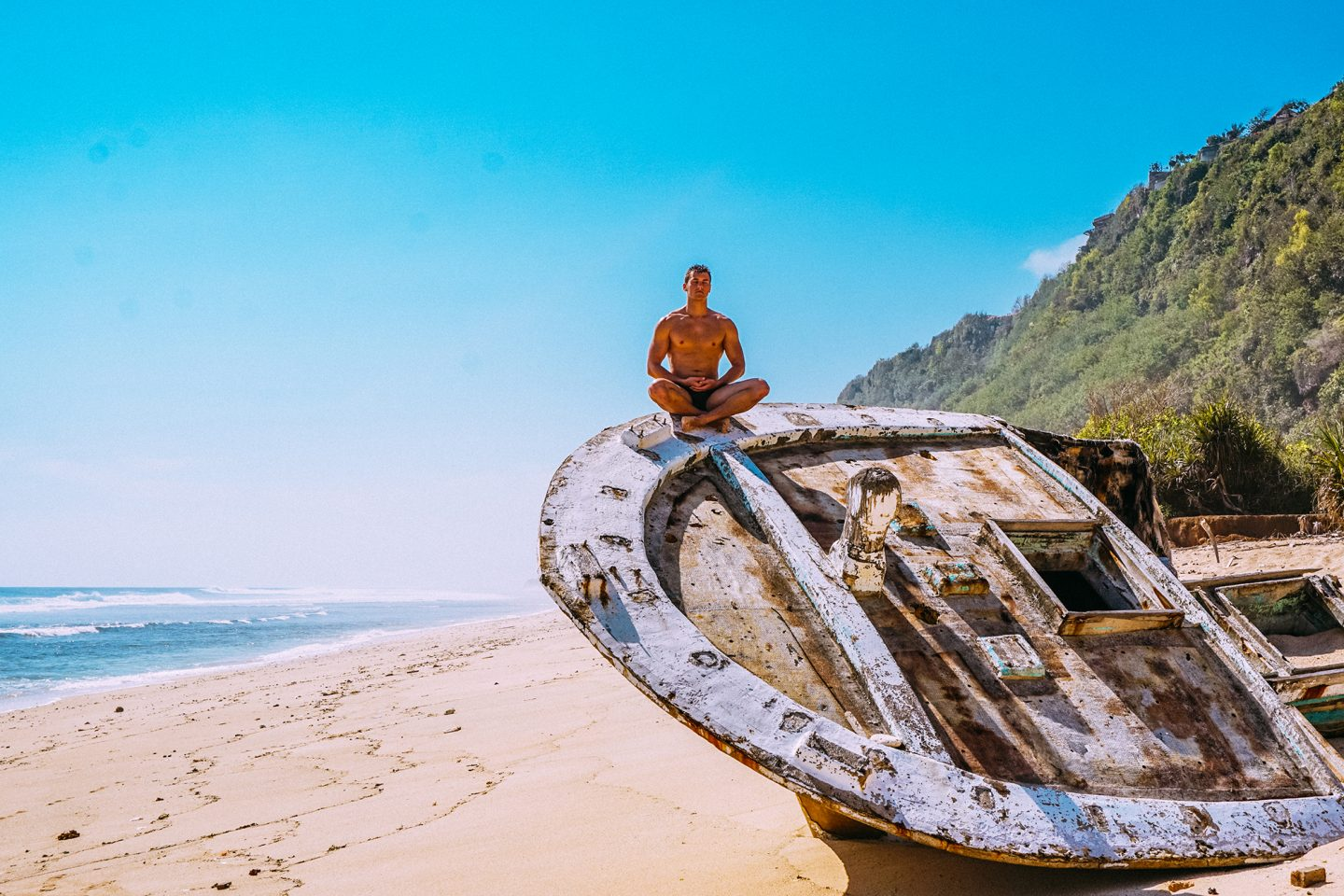 Guy sitting on a wooden boat at the beach.