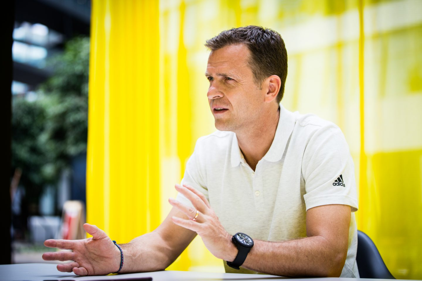 Oliver Bierhoff, Manager German national football team wearing white poloshirt talking during an interview in front of a yellow background, Oliver Bierhoff_DFB_interview_adidas_GamePlan A