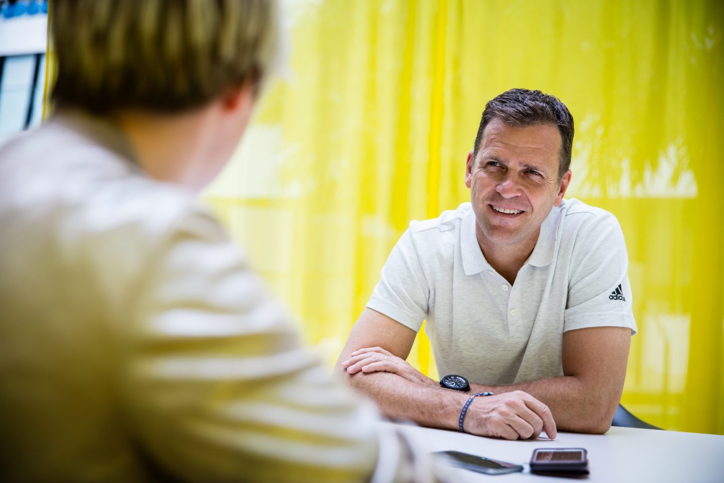 Oliver Bierhoff wearing a white poloshirt smiling at the interviewer in front of yellow background, Oliver Bierhoff_Interview_DFB_Manager_adidas_GamePlan A