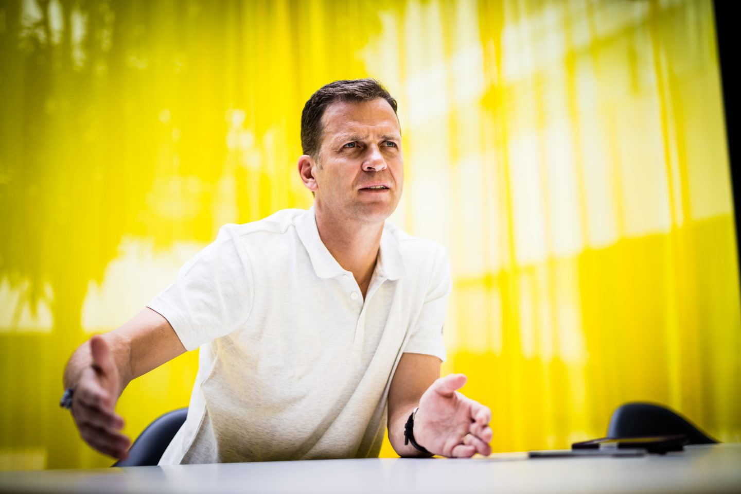 Oliver Bierhoff wearing white poloshirt giving an interview in front of yellow background at adidas for GamePlan A on team culture and the German national team, Oliver Bierhoff_DFB_Interview_adidas_Team Culture