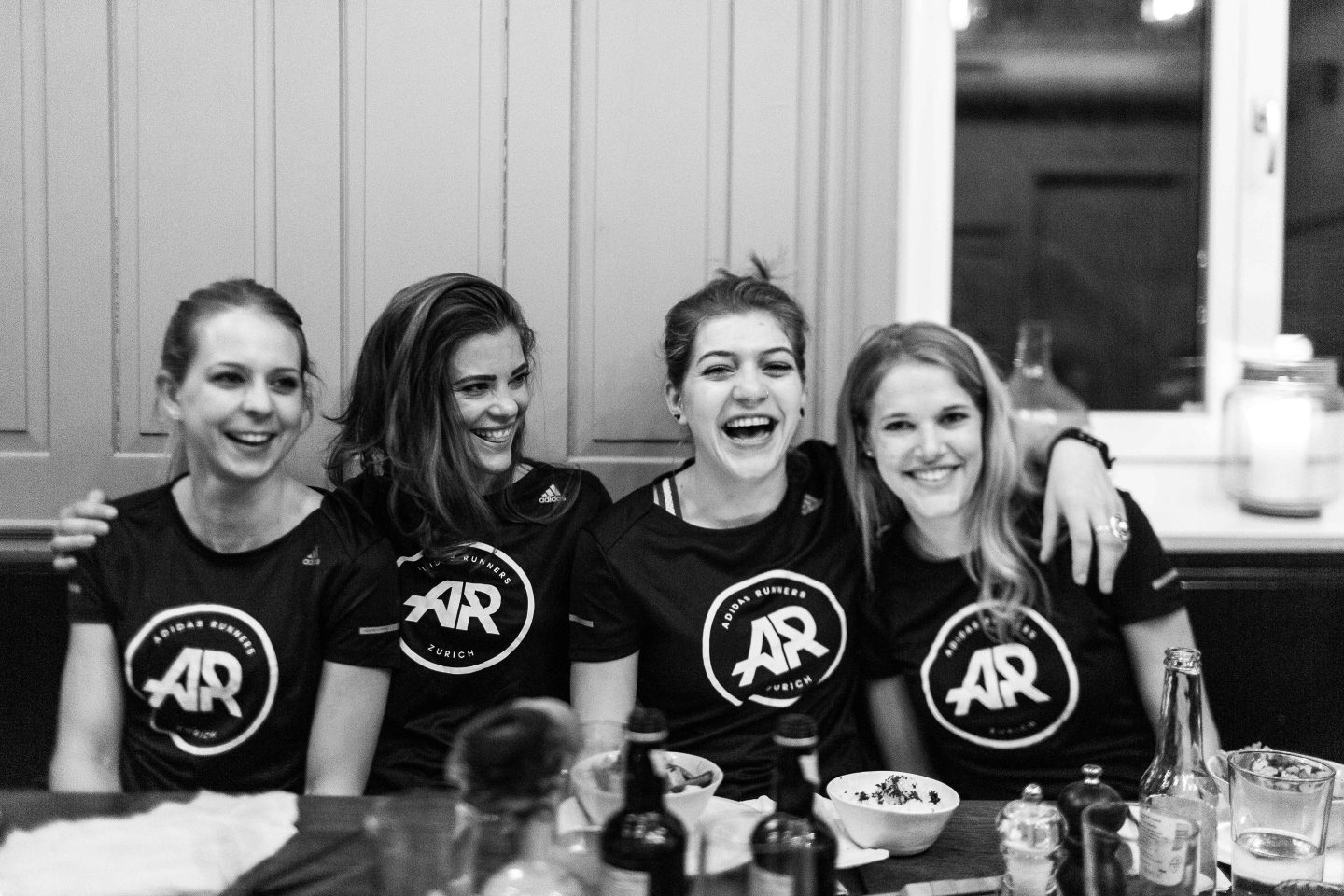 Black and white picture women in running tshirts laughing and sitting on a restaurant table, adidas, Running, adidas Runners, girls, laughing, friends, marathon, GamePlan A