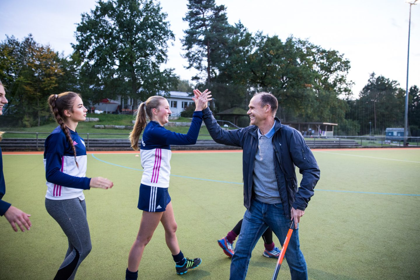 The coach is high-fiving his female players.