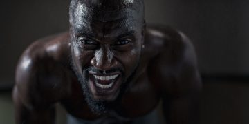 A shirtless man is bent forward in deep concentration as he focuses on his strength training with deep creases along his forehead.