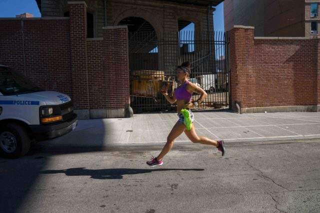 Robin Arzon running under a bridge on a city street.