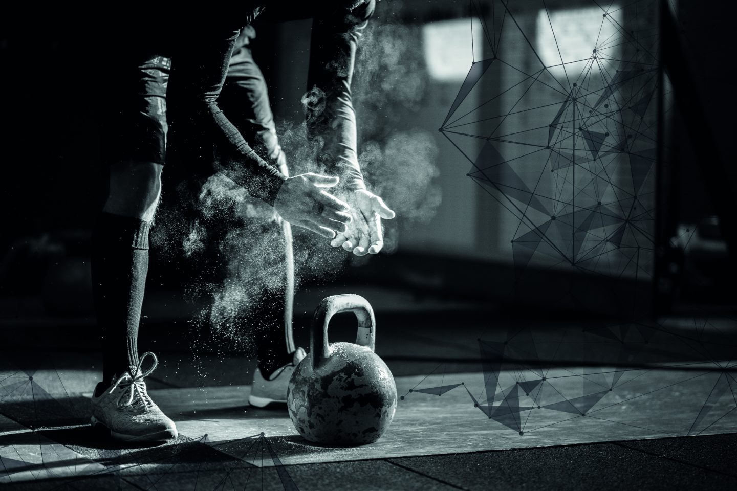 Hands in a puff of a chalk cloud a pair of hands reaches for a kettle bell.