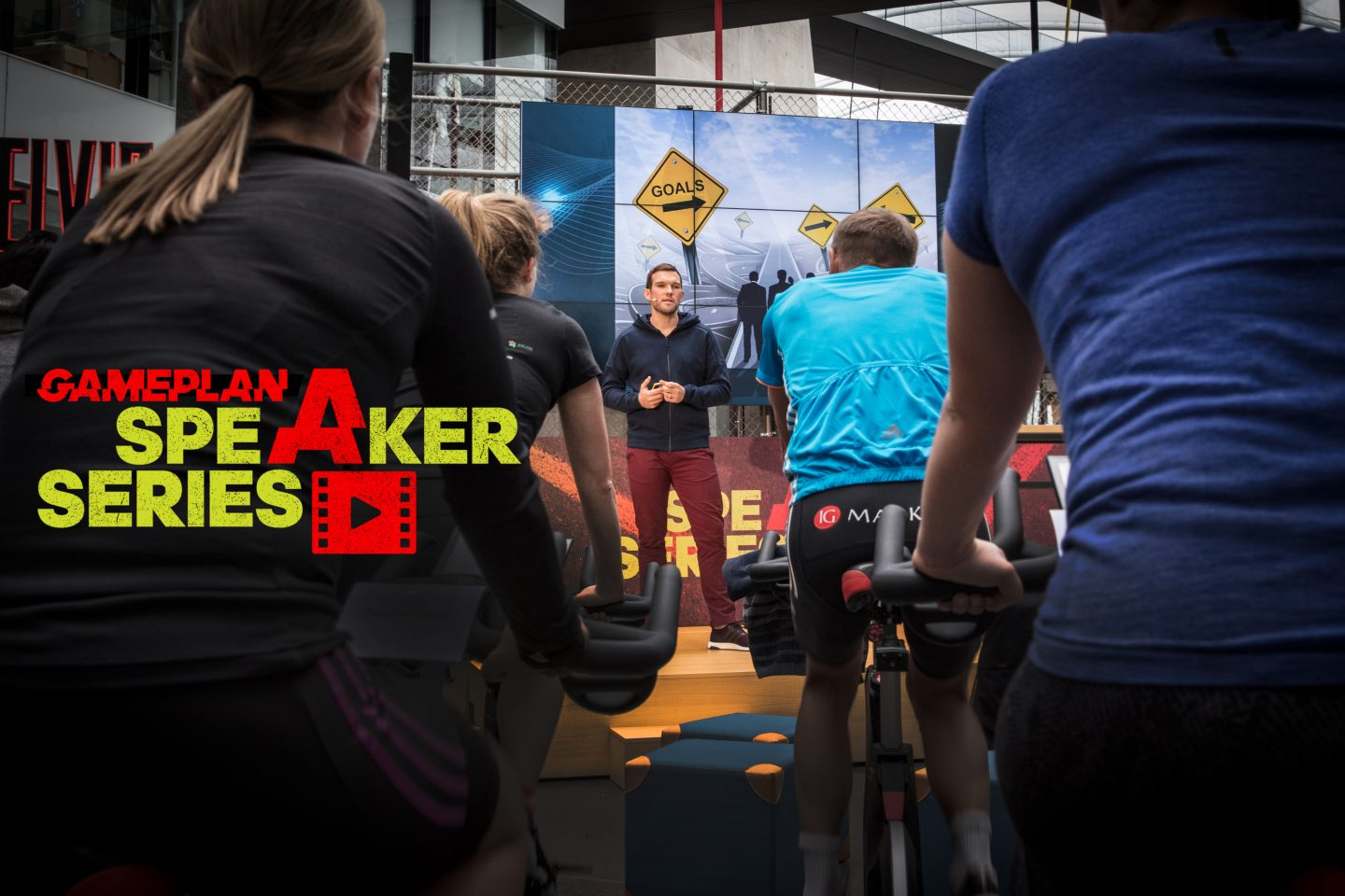 Man standing on stage delivering a speech in front of a group of indoor cyclists at the adidas HQ. GamePlan A, Marcus Leach, Speaker Series, goal-setting, success, public speaking, cycling, motivation