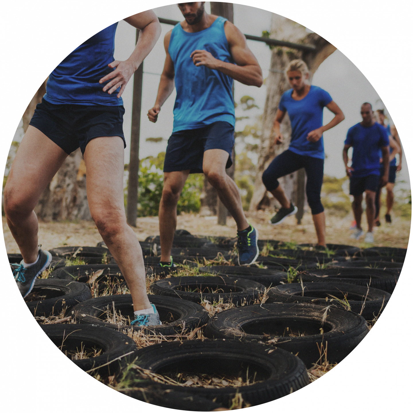 Sporty people running through an obstacle parcours with old car tires. team building, obstacle race, team event, business, fitness, bonding, Outdoor_Fitness Circuit_Obstacle race, adidas, GamePlan A