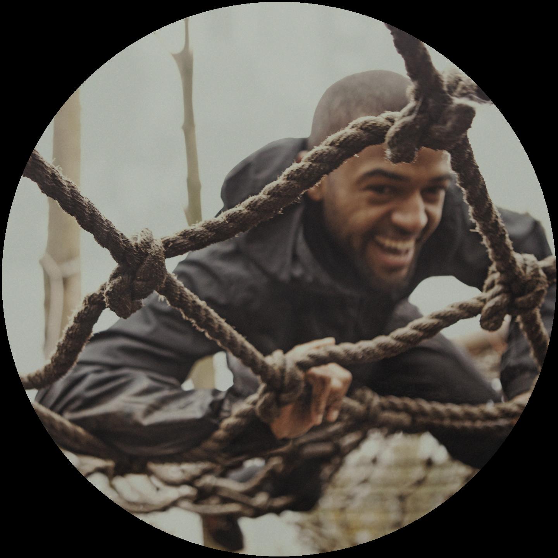 A man climbing on a net during an obstacle race. team building, team event, Obstacle Race_team building_climbing a net