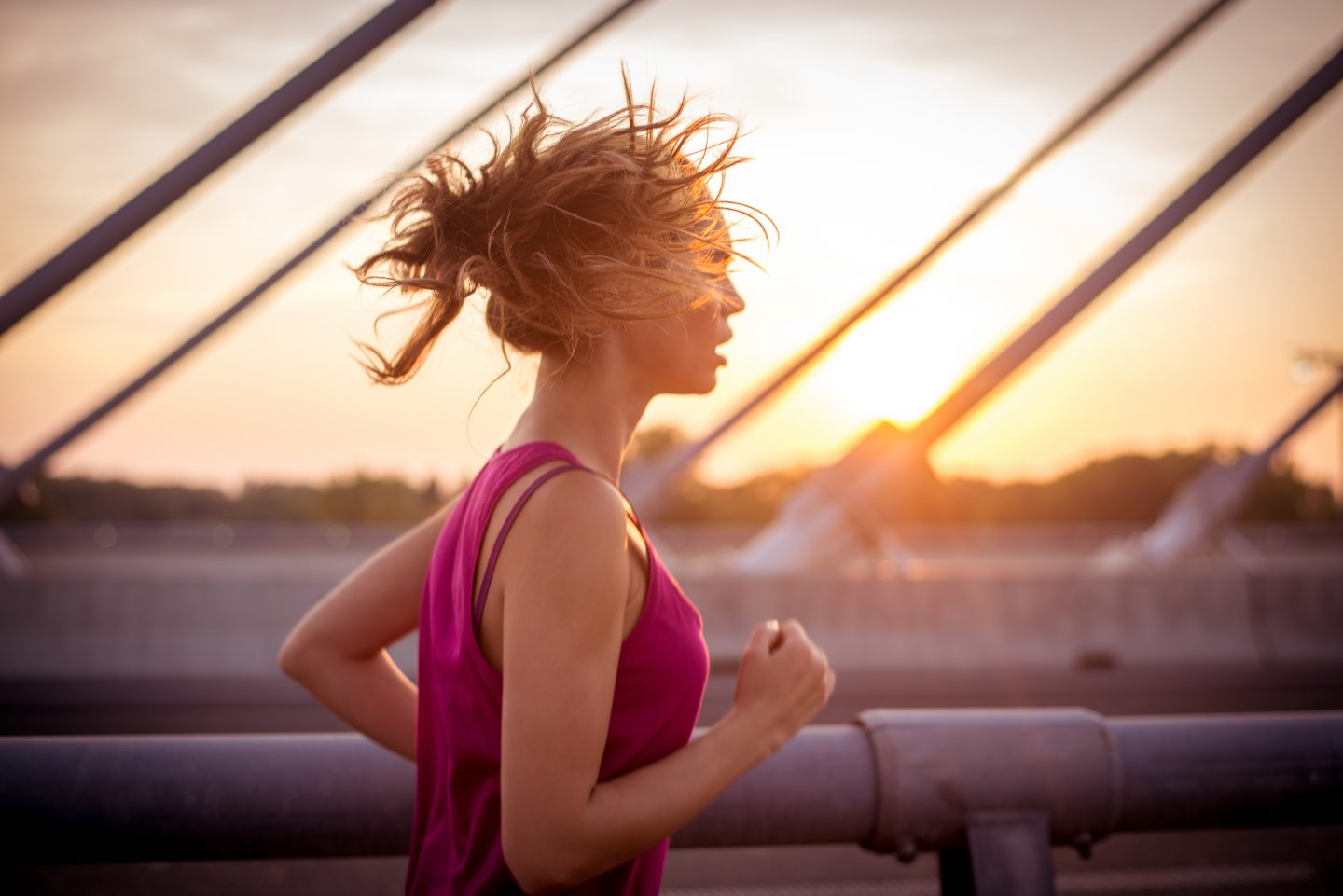 Young sportswoman jogging over the bridge in the morning while her long brown hair is waving in the wind. Rising sun is in the background.