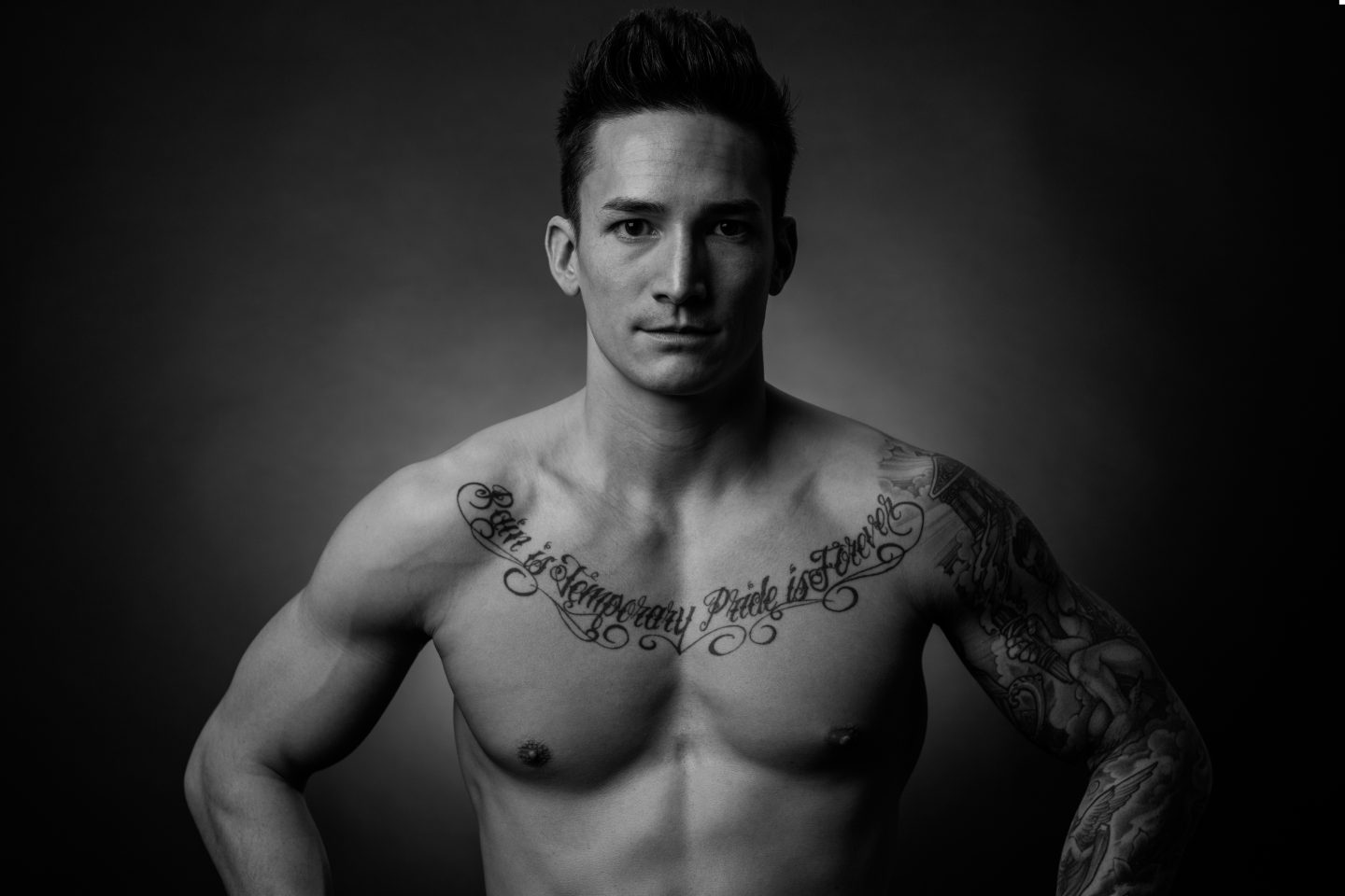 Gymnast Marcel Nguyen is facing the camera. The tattoo on his bare chest reads