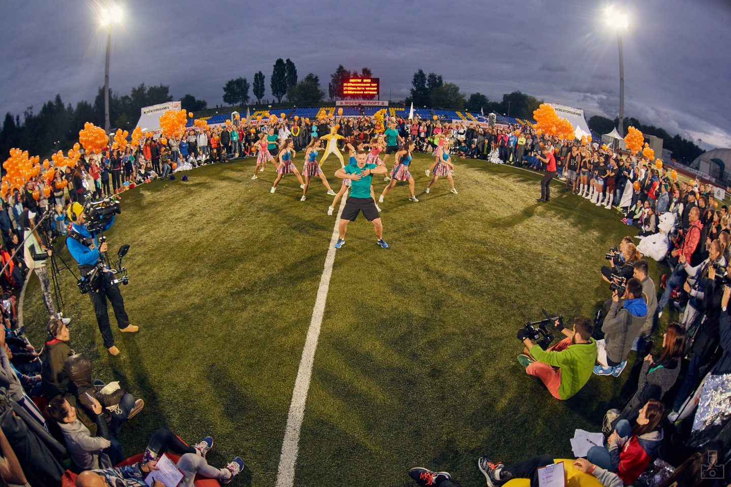 A group of cheerleaders and an athlete are performing on a field surrounded by a big crowd. Dance; Field; Motivation; Passion; Collaboration; adidas; Reebok; GamePlan A