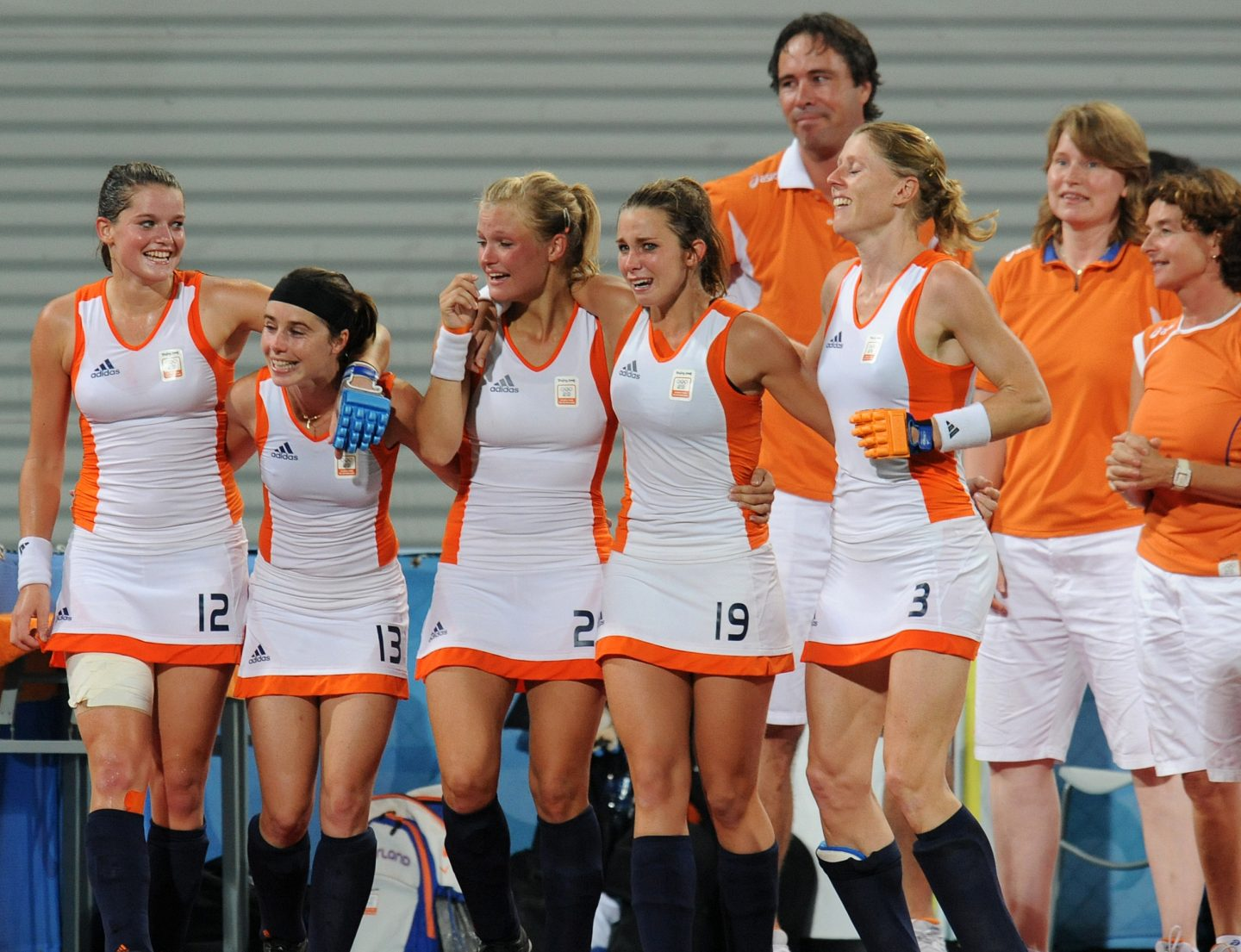 five teammates of the Dutch women's hockey team gathering after winning a match