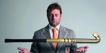 Business and hockey coach Marc Lammers posing for a picture with a hockey stick wearing a business suit