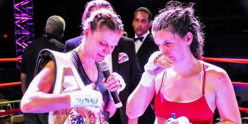 Lisa Garland is in the boxing ring, holding a microphone and a world champions belt. Boxing; Motivation; Adidas; GamePlanA; Fight; Champion; Goals