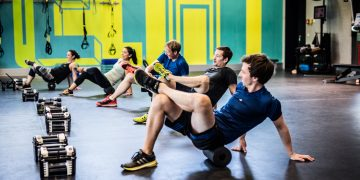 A group of people is working out in a gym room using foam rolls. Exos; Motivation; Gym; Workout; Team; Group Training; adidas
