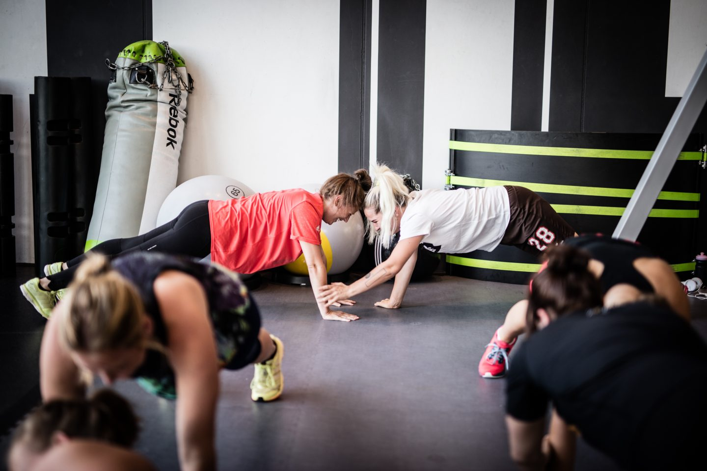 A group of people are in plank position during a workout while two women are seen performing the exercises as partners. Workout; Fitness; Gym; Motivation; Dedication; Teamwork; Partner; Reebok; Adidas; GamePlan A