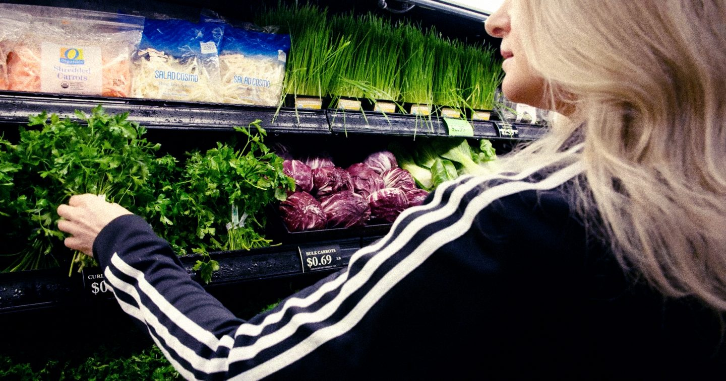 Blonde woman in a black adidas sweater with three stripes buys cilantro