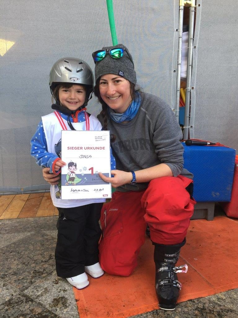 Girl gets her record from her skiing instructor and is smiling